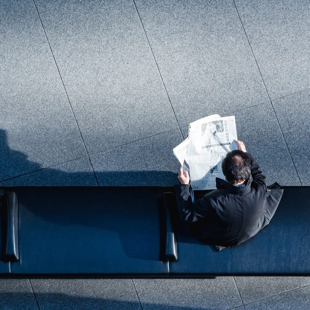 man reading newspaper on bench from above